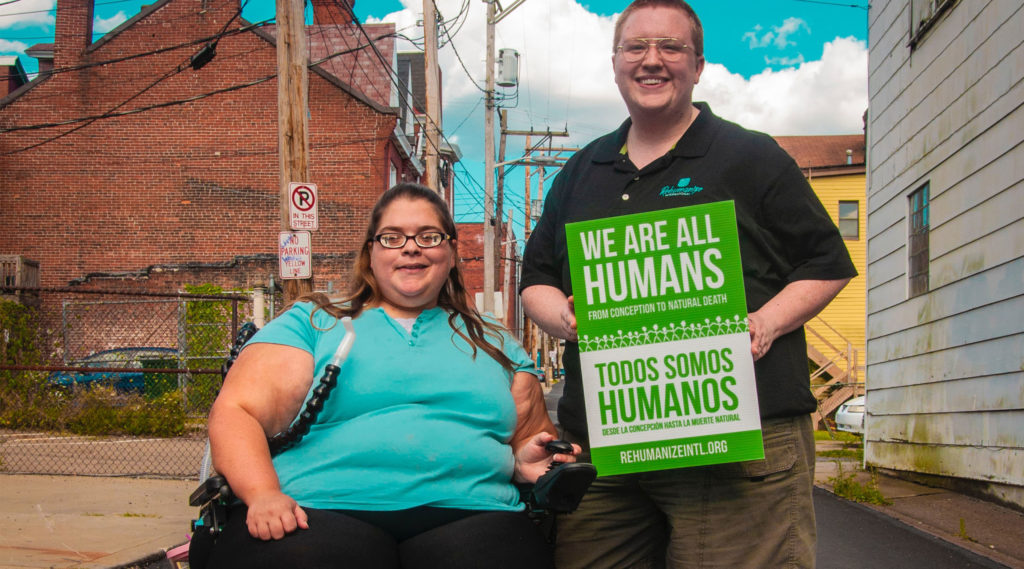 "Two people smile, one standing and one in a wheelchair, and hold a sign that says ""we are all humans from conception to natural death"" in English and Spanish."