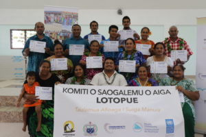 Family Safety Committee members from the village of Lotopue smiling for a photo with their certificates of completion