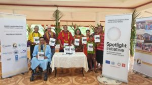 Family Safety Committee members smiling for a photo in a room with programme booklets, surrounded by pull-up banners showing the UN Spotlight Initiative logo